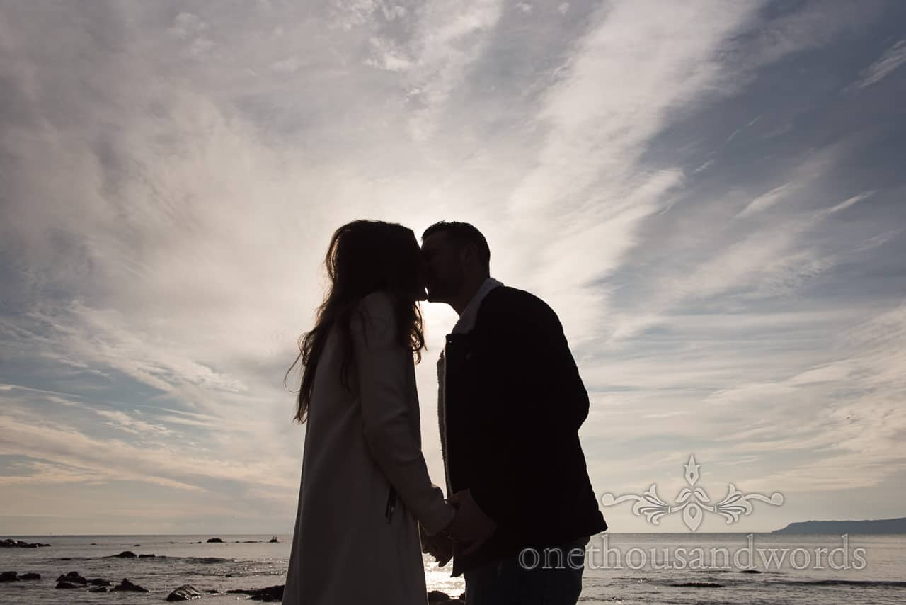 Osmington Mills engagement photographs couple kissing in silhouette against blue sky by one thousand words photography