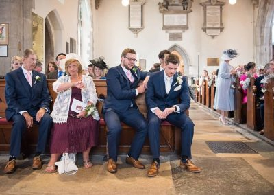 Photojournalist wedding image of groom checking time on wrist watch in Swanage church wedding venue by one thousand words