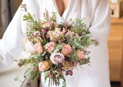 Pink, purple and white flowers in wedding bouquet with green foliage detail photograph by one thousand words photography