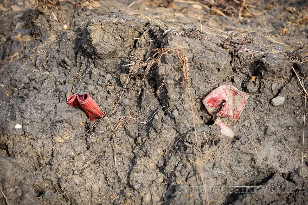 Red wellington boots stuck in clay mud on Dorset beach by one thousand words documentary wedding photography