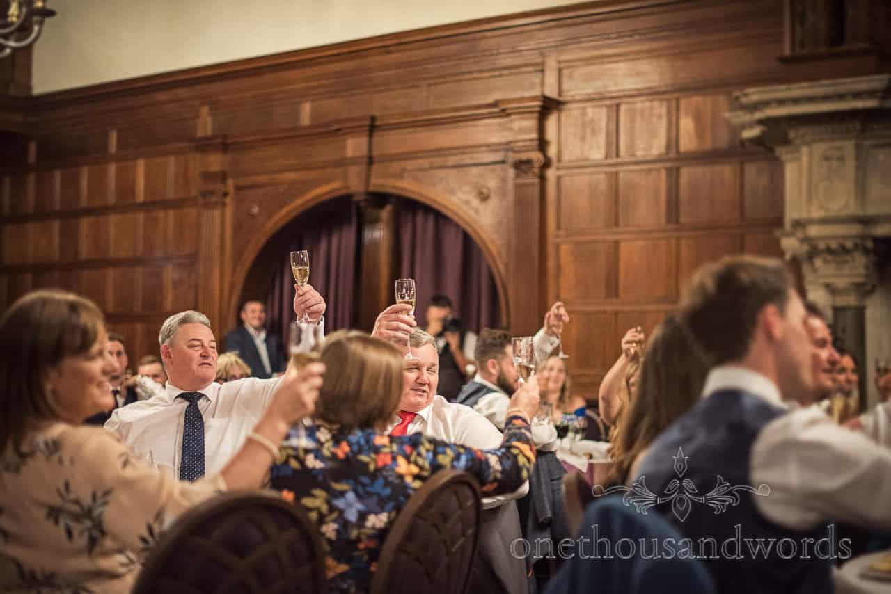 Glasses raised by guests at Rhinefield House wedding speeches toasts photograph by one thousand words wedding photography