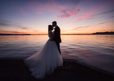 Seaside sunset wedding couple kissing silhouette documentary photograph in Poole harbour in Dorset by one thousand words