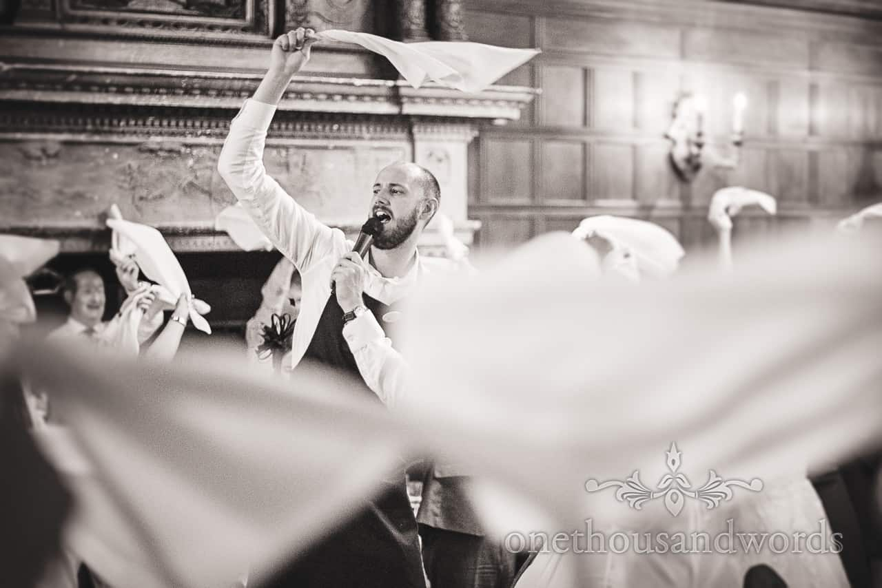 Black and white photograph of singing waiter during wedding entertainment performance with swirling napkins