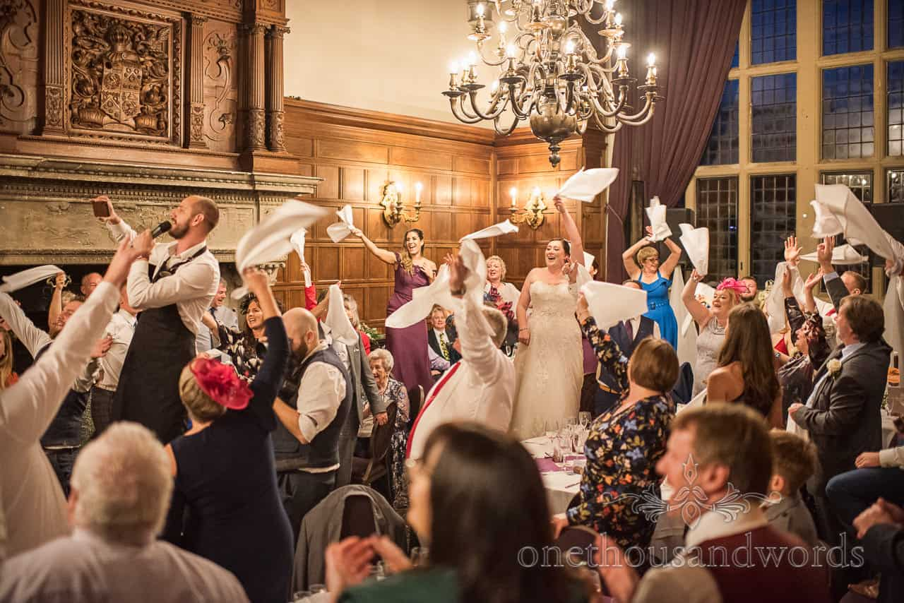 Bride and wedding guests join in with singing waiter during performance at wedding at Rhinefield House Hotel