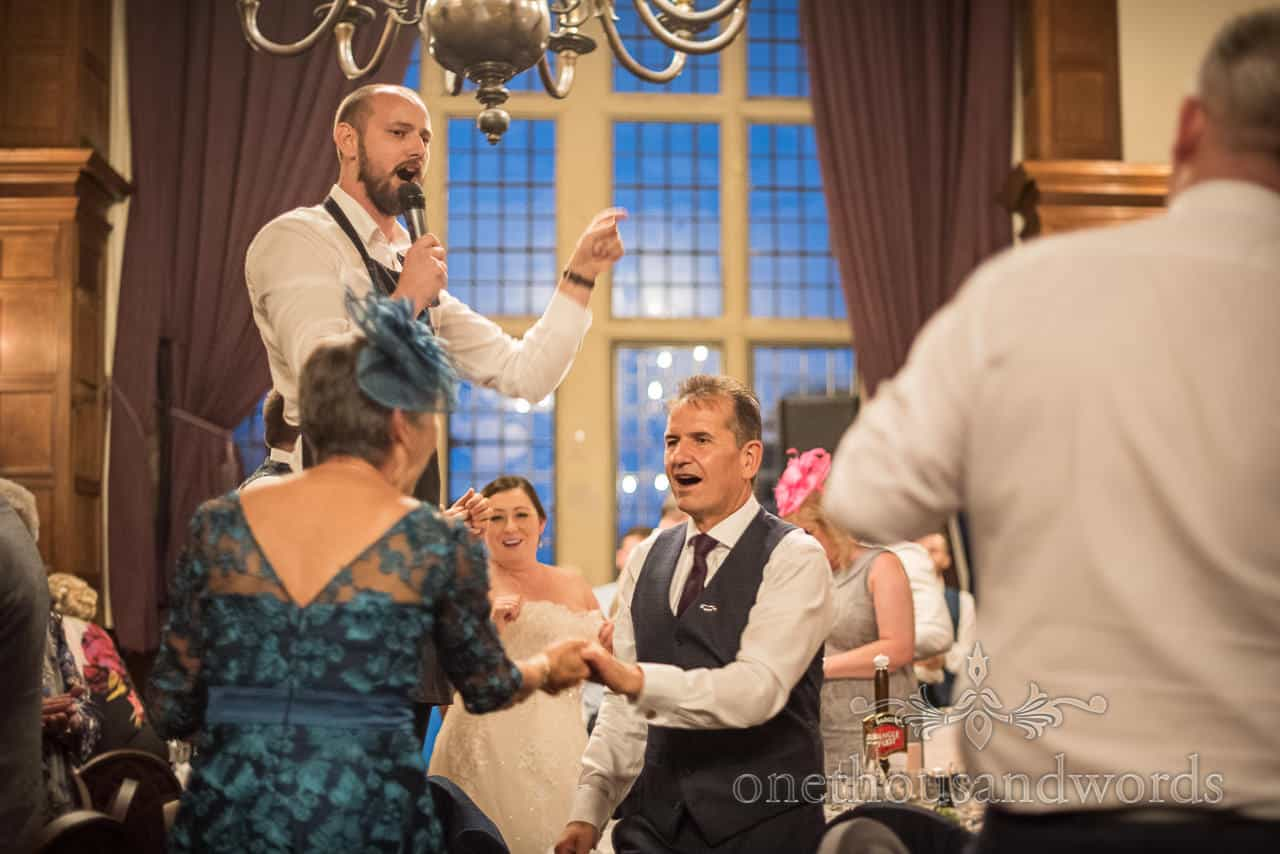 Wedding guests dance with singing waiter at New Forest hotel wedding photographs by one thousand words documentary photography