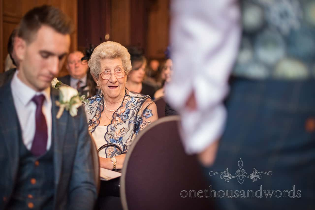 Smiling grandma watches groomsmen before New Forest hotel wedding ceremony photographs by one thousand words photography