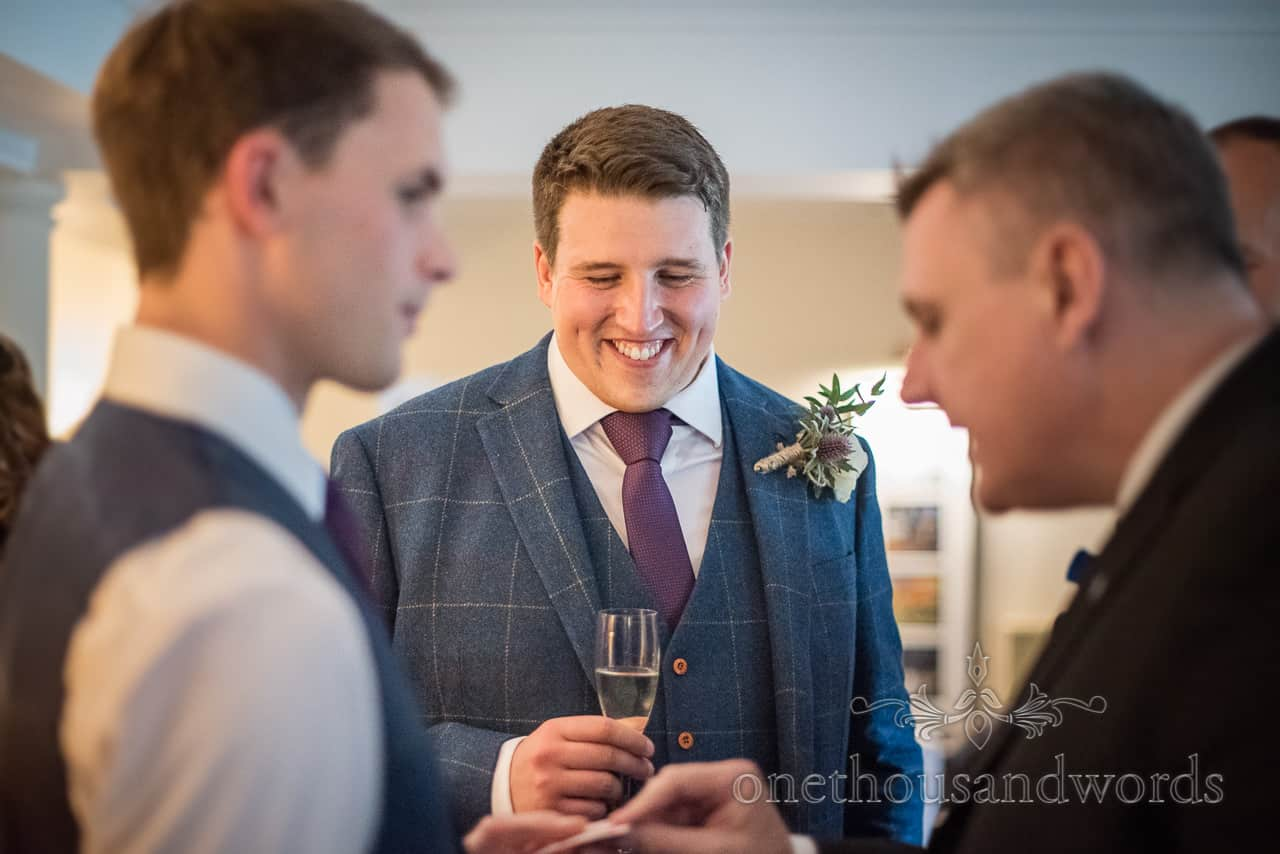 Happy groom with champagne glass watches wedding magician entertain guests at drinks reception photograph by one thousand words