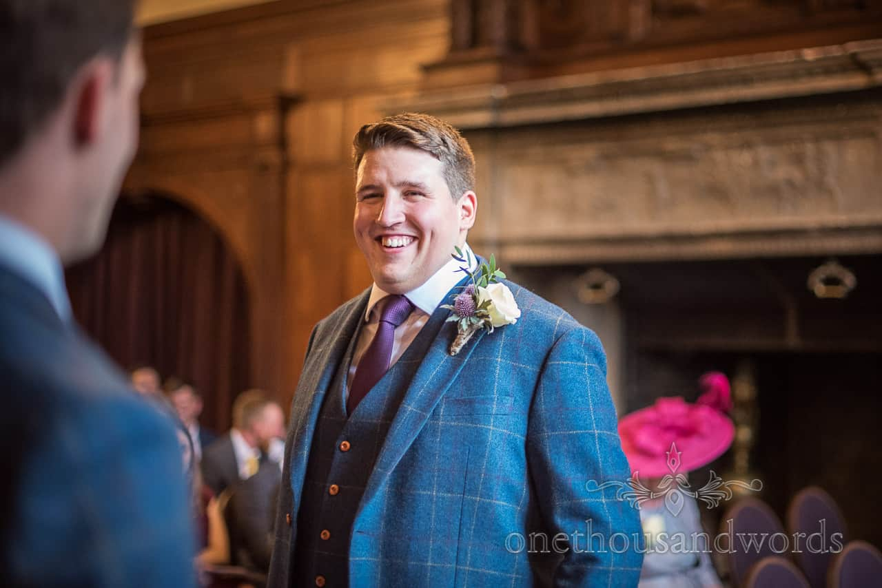 Smiling groom wears three-piece blue check tweed wedding suit before wedding ceremony at Rhinefield House Hotel venue