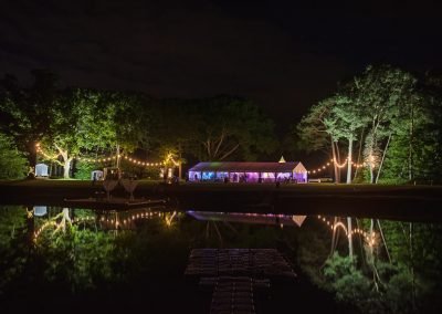 Sopley Lake Dorset wedding venue marquee glowing at night with festoon lighting reflection