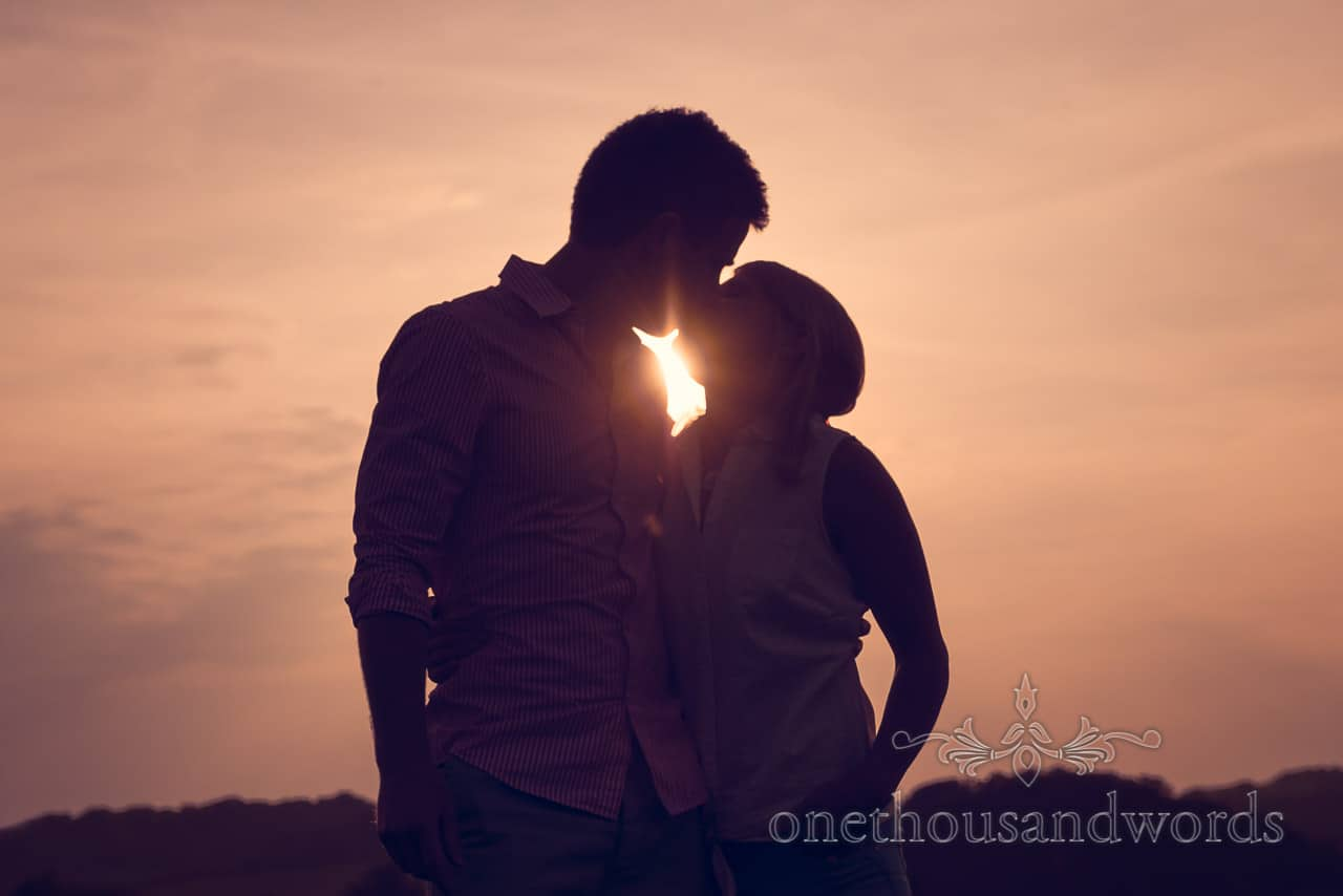 Top tips for engagement photos time of day shown by couple kissing at sunset