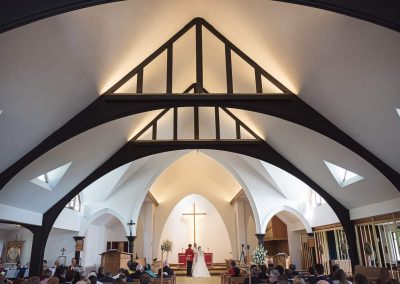 Symmetrical black and white church roof in Dorset with bride and groom at the altar at wedding venue ceremony