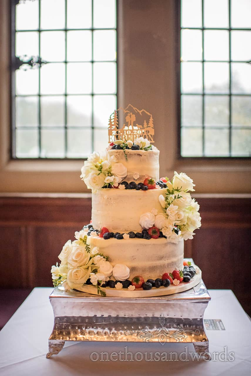 Three-tier iced naked wedding cake with fresh fruit wedding photograph by one thousand words wedding photography