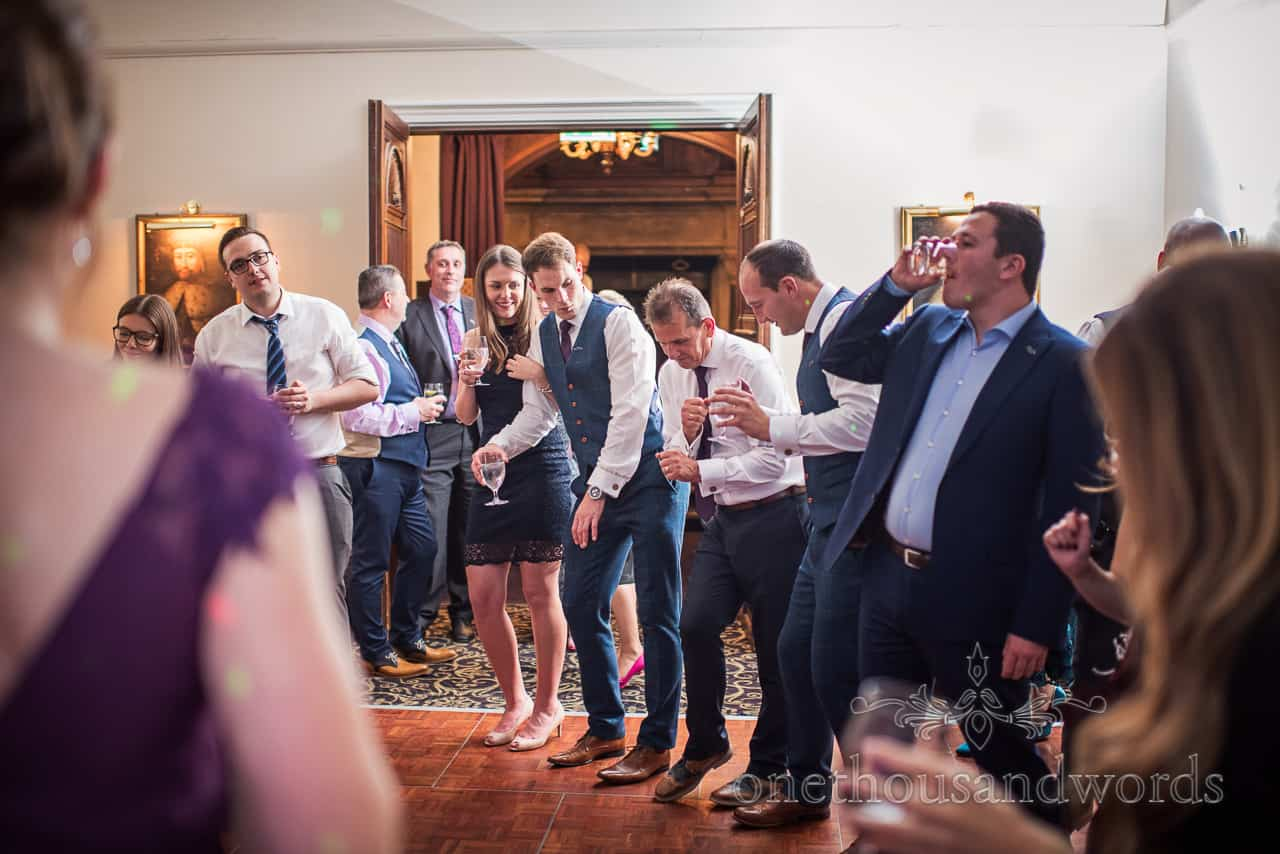 Wedding guests dancing shapes at Rhinefield House Hotel wooden dance floor documentary wedding photo by one thousand words