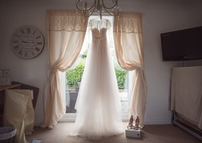 Wedding dress hangs in bedroom window wedding morning photograph by Dorset photographers one thousand words