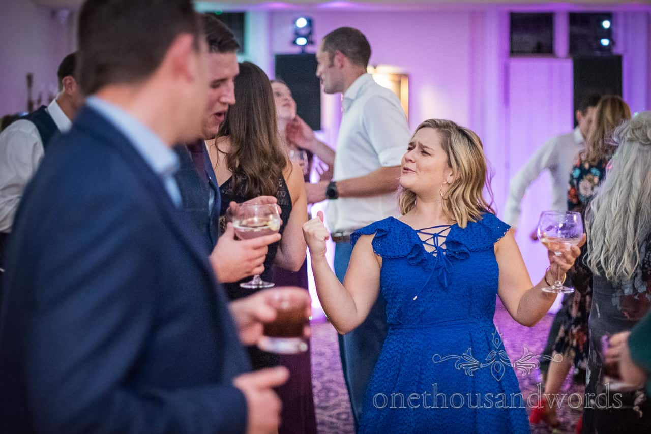 Singing wedding guest in blue dress dancing with drinks in hand on dance floor with disco lights in New Forest