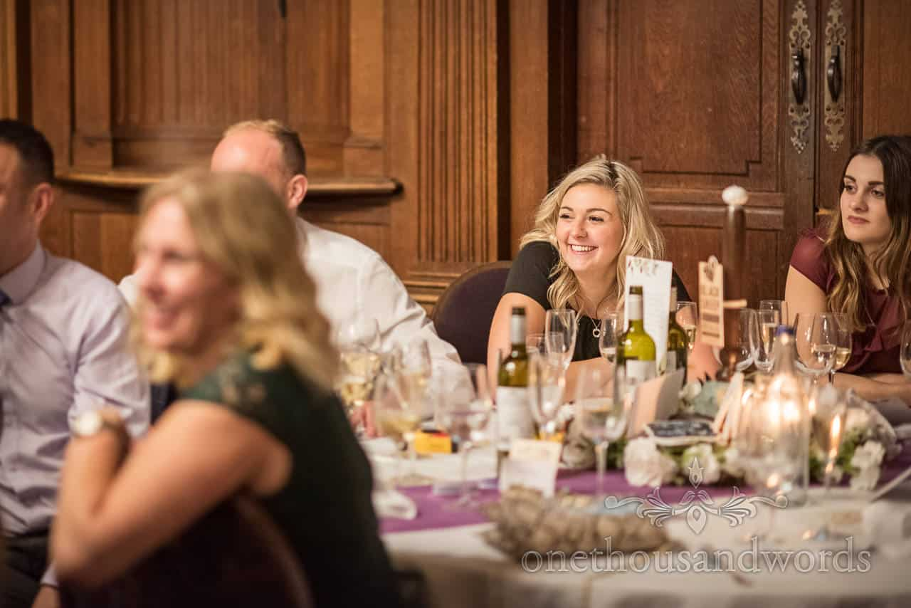 Happy wedding guest smiles during wedding breakfast speeches at Rhinefield House Hotel in New Forest