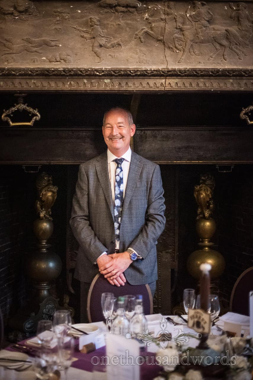Happy wedding guest stands in large fireplace at Rhinefield House Hotel