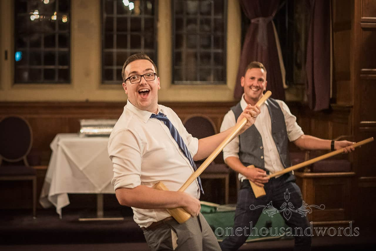 Funny wedding photograph of wedding guests play air guitar with croquet mallets at an evening reception at Rhinefield House