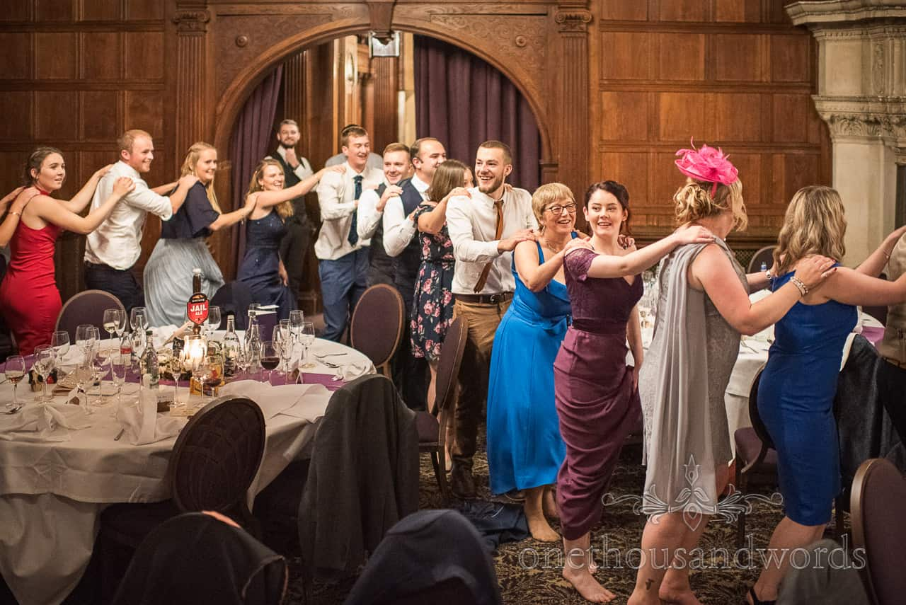 Wedding guests form conga line led by singing waiter at Rhinefield House Hotel wedding venue in New Forest
