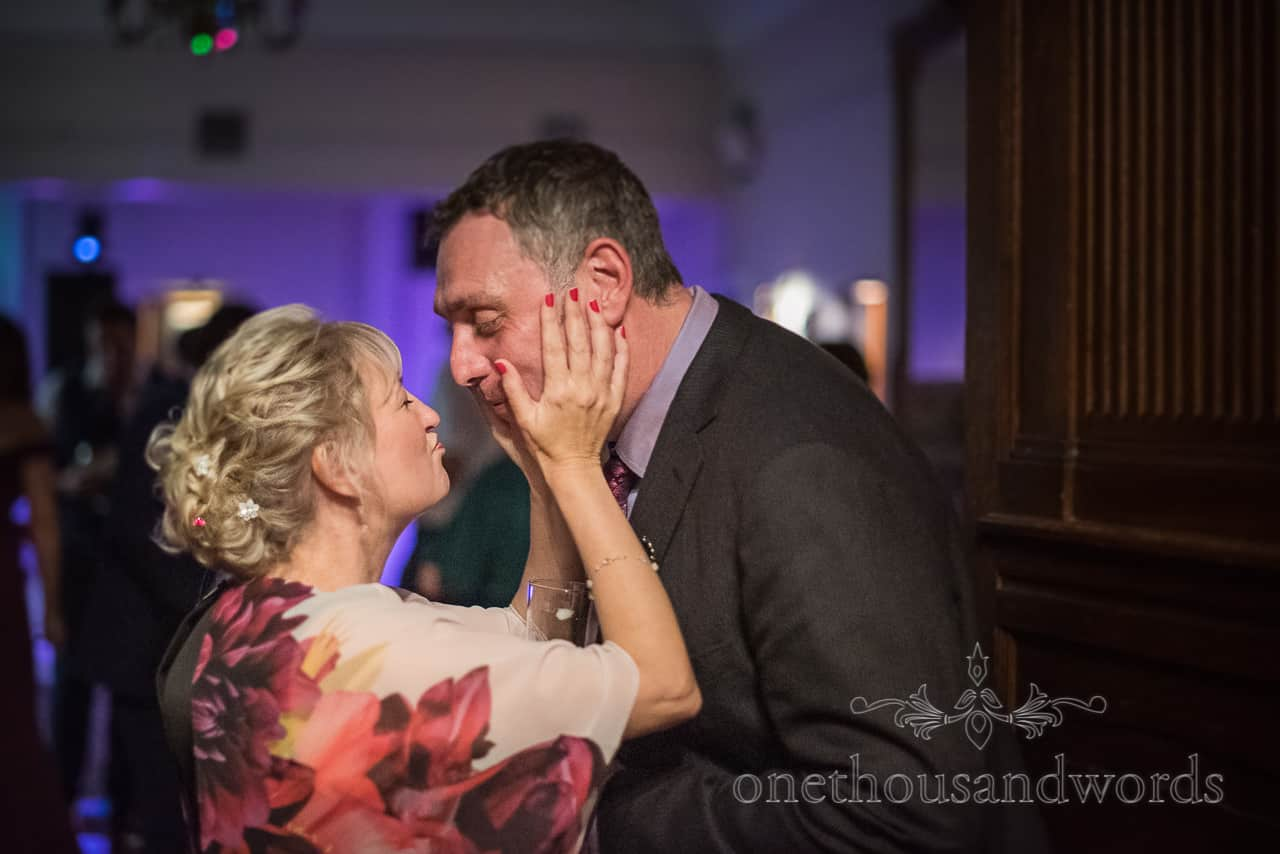 Wedding guests pucker up for kiss in doorway by one thousand words documentary wedding photographers at Rhinefield House