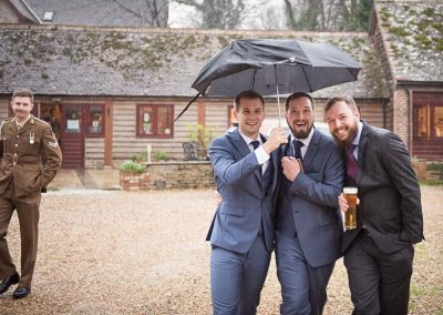 Wedding guests shelter from rain under umbrellas whilst being watched by and unimpressed best man in green military uniform