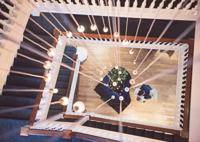 Wedding photograph of Balmer Lawn wedding venue staircase piano and lights taken from above by one thousand words photography