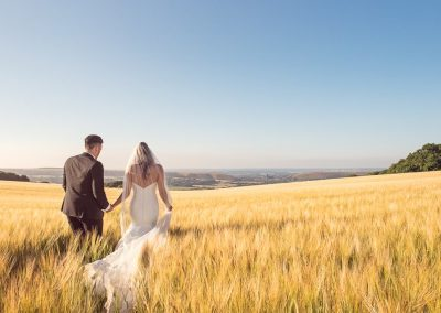 Wedding photograph of bride and groom walking in Dorset countryside golden barley field by one thousand words wedding photography