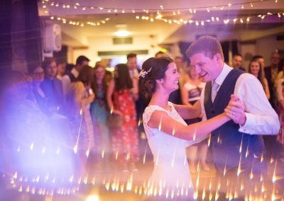 Wedding photograph of first dance with fairy lights and coloured disco lighting at Dorset wedding venue by one thousand words
