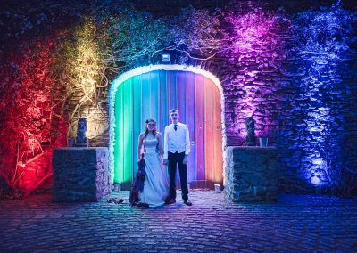 Wedding photograph of bride and groom at Walton Castle with multicoloured up lighters in wooden doorway by one thousand words