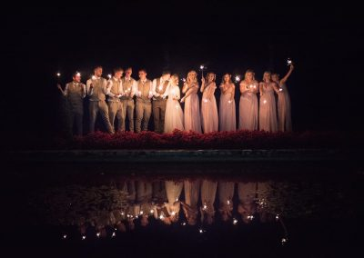 Photograph of groomsmen and bridesmaids with bride and groom holding sparklers reflected in lake at night