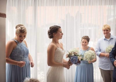 Wedding photograph of nervous bride and excited bridesmaids before wedding ceremony by one thousand words photography