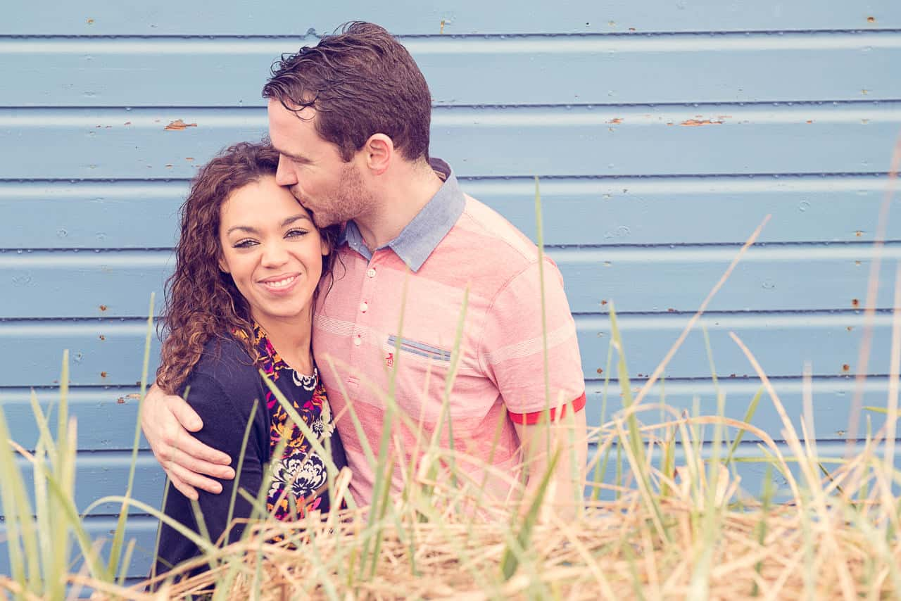Happy couple kiss at wooden beach hut engagement photo shoot