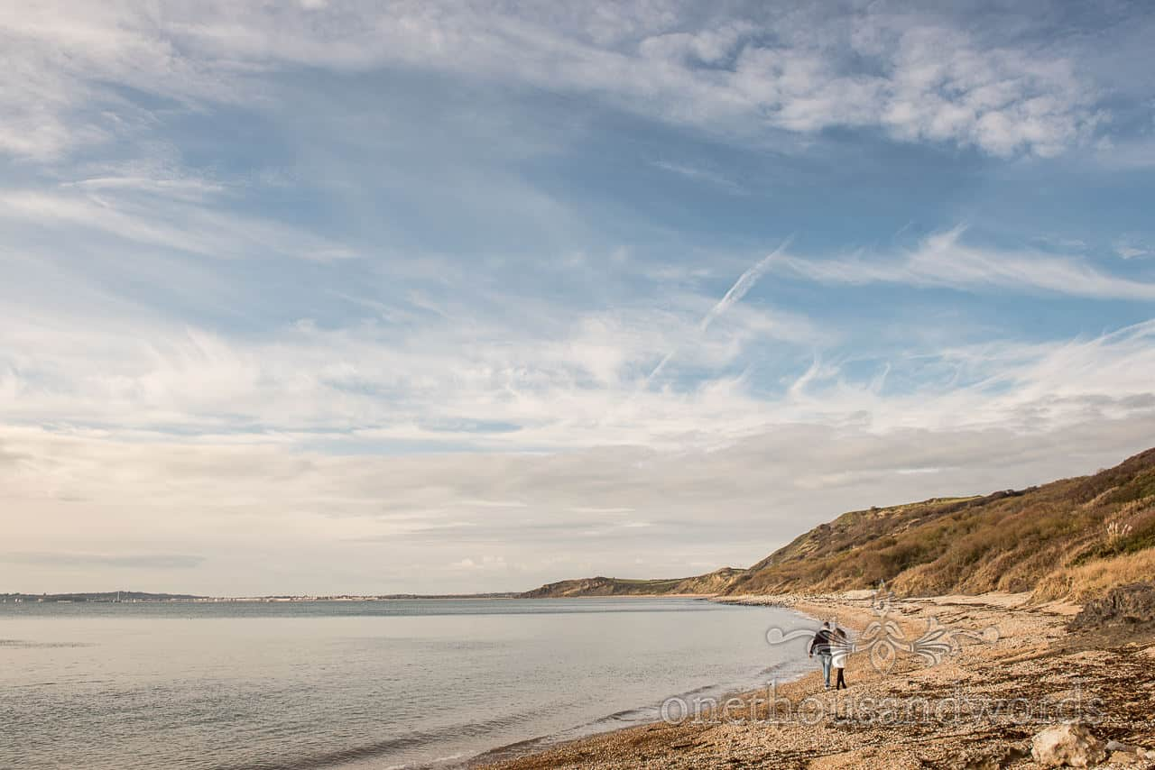 Wide angle photograph of engagement couple walking along Dorset beach by one thousand words wedding photography
