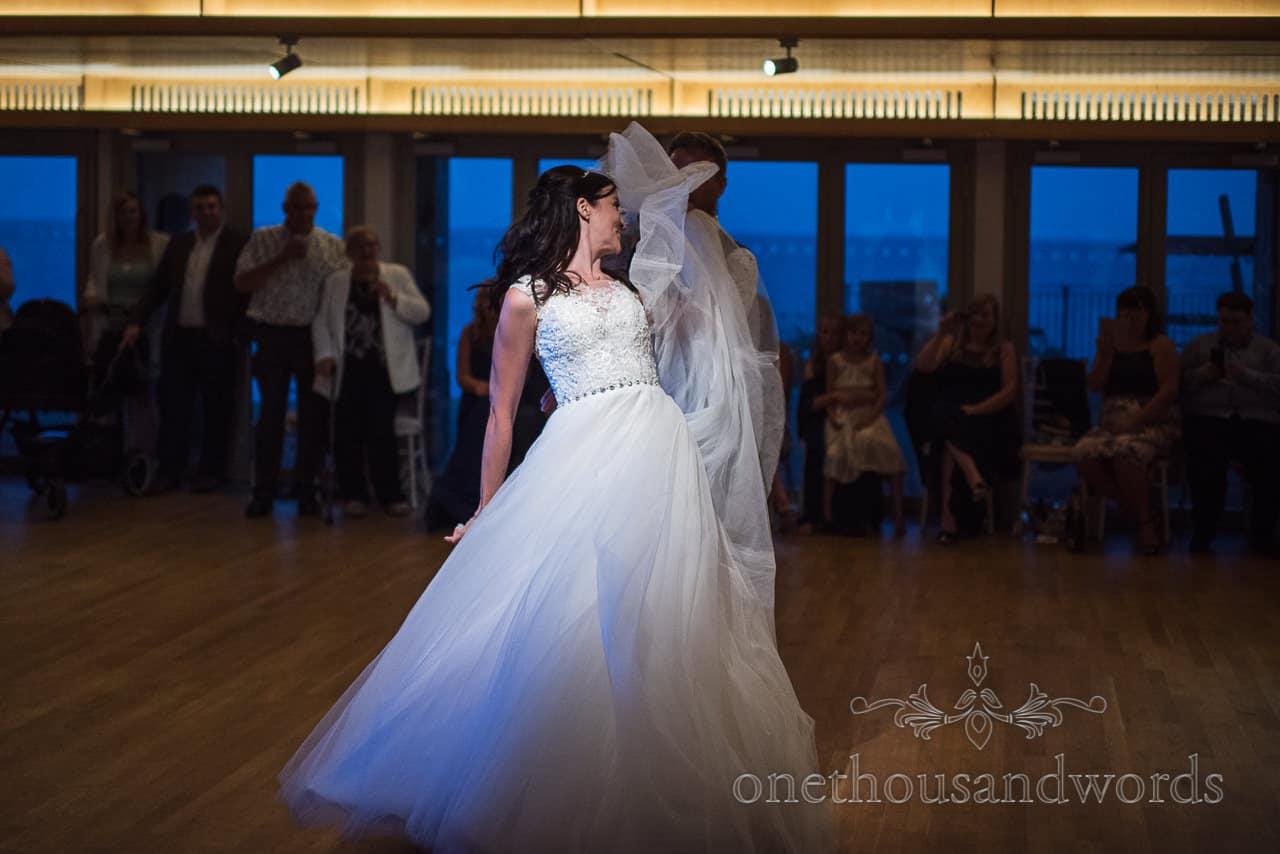 Brides white wedding dress swirls under a spotlight during a first dance routine on the wooden dance floor