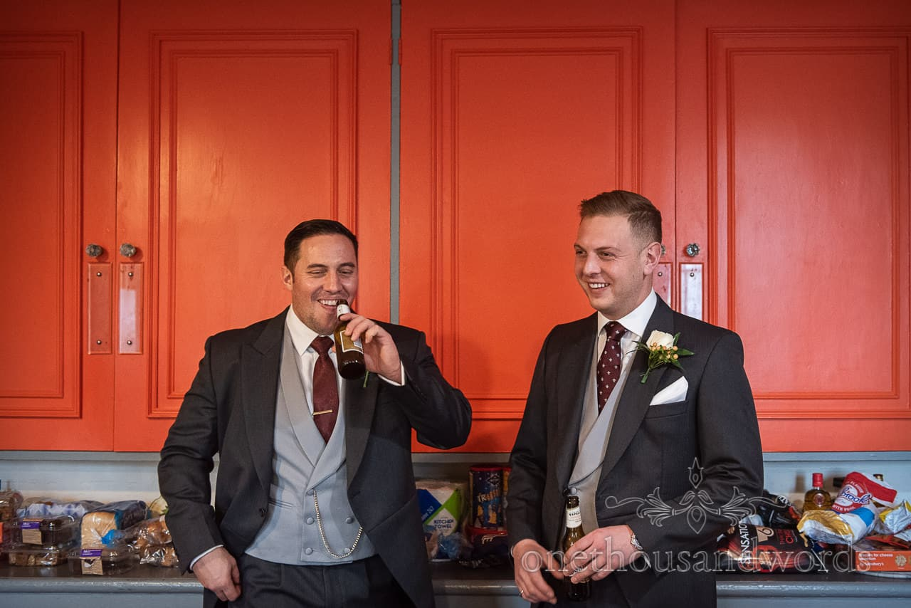 Best man and groom Enjoy last drink in kitchen before Smedmore House wedding ceremony