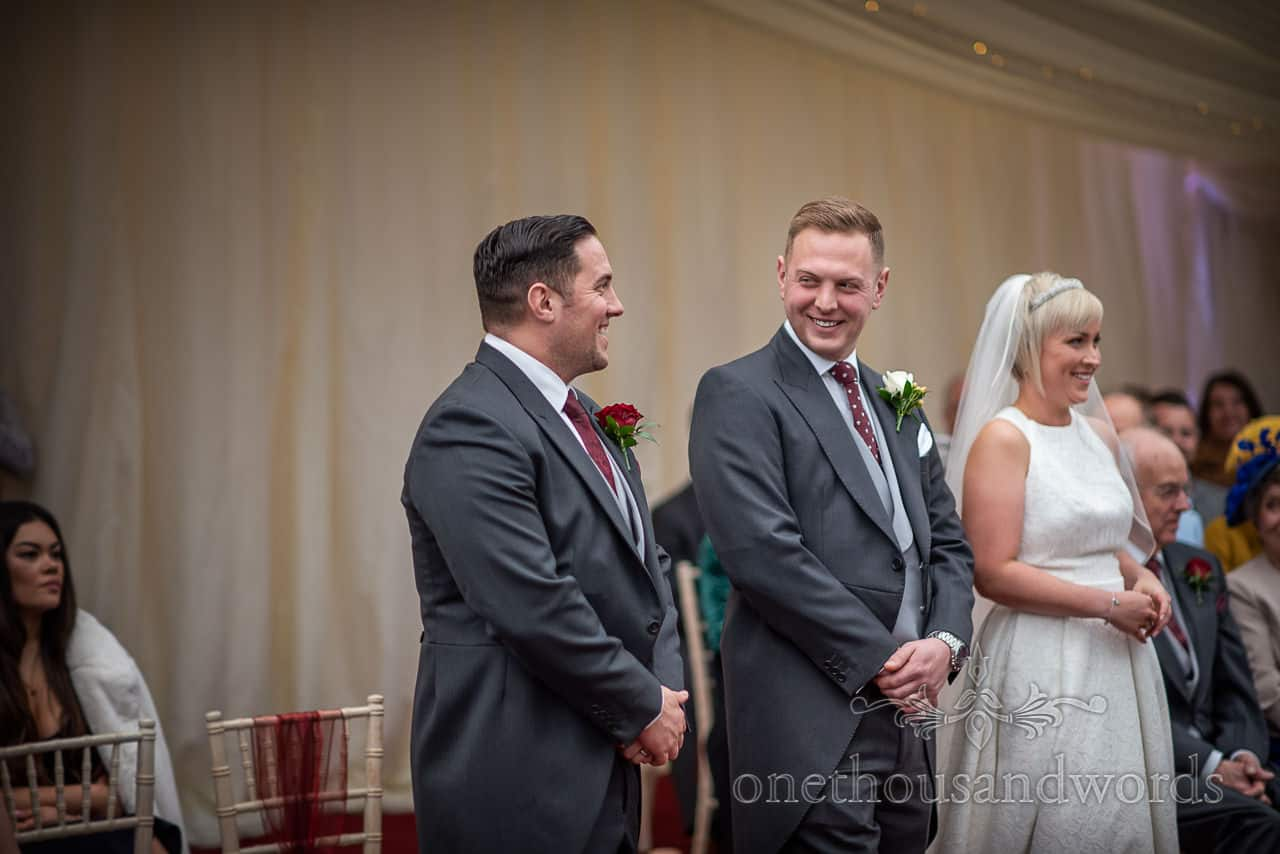 Best man and groom share a moment during Smedmore House wedding ceremony