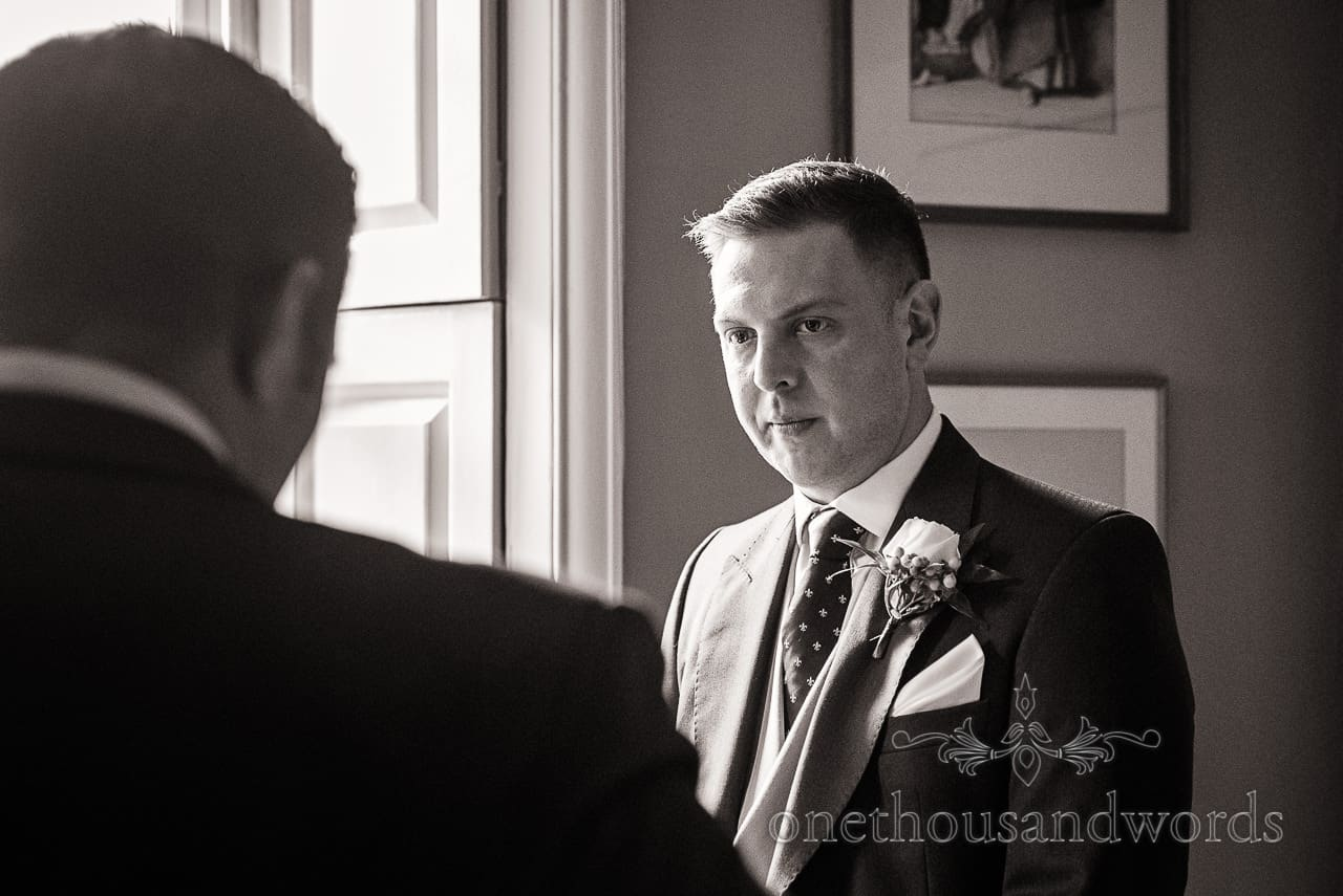 Black and white groom portrait by window from Smedmore House wedding photographs