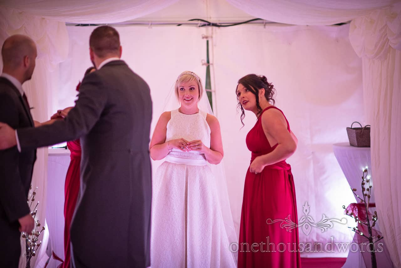 Bride, bridesmaid and groomsman discussion during marquee reception at Smedmore House