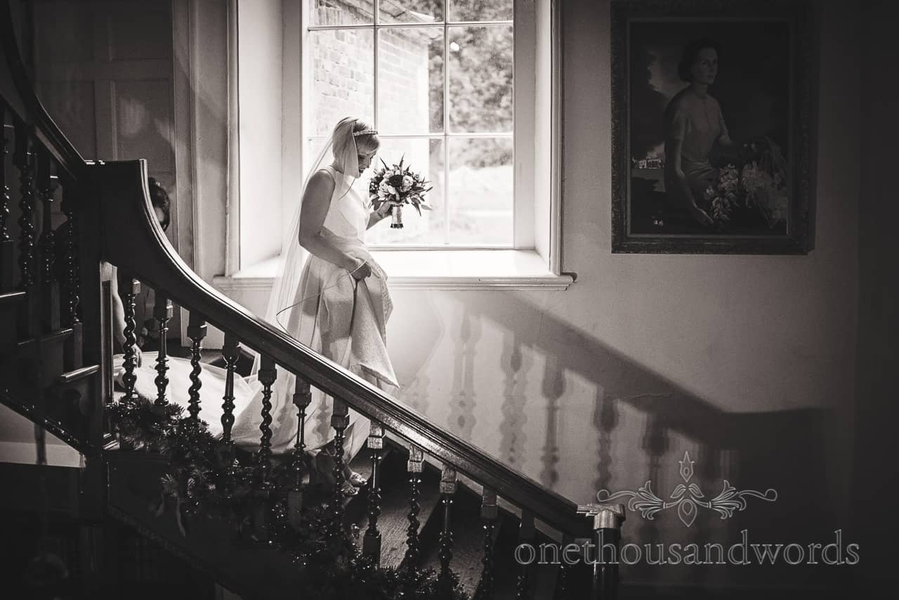 Bride on wooden staircase in white wedding dress at Smedmore House Wedding