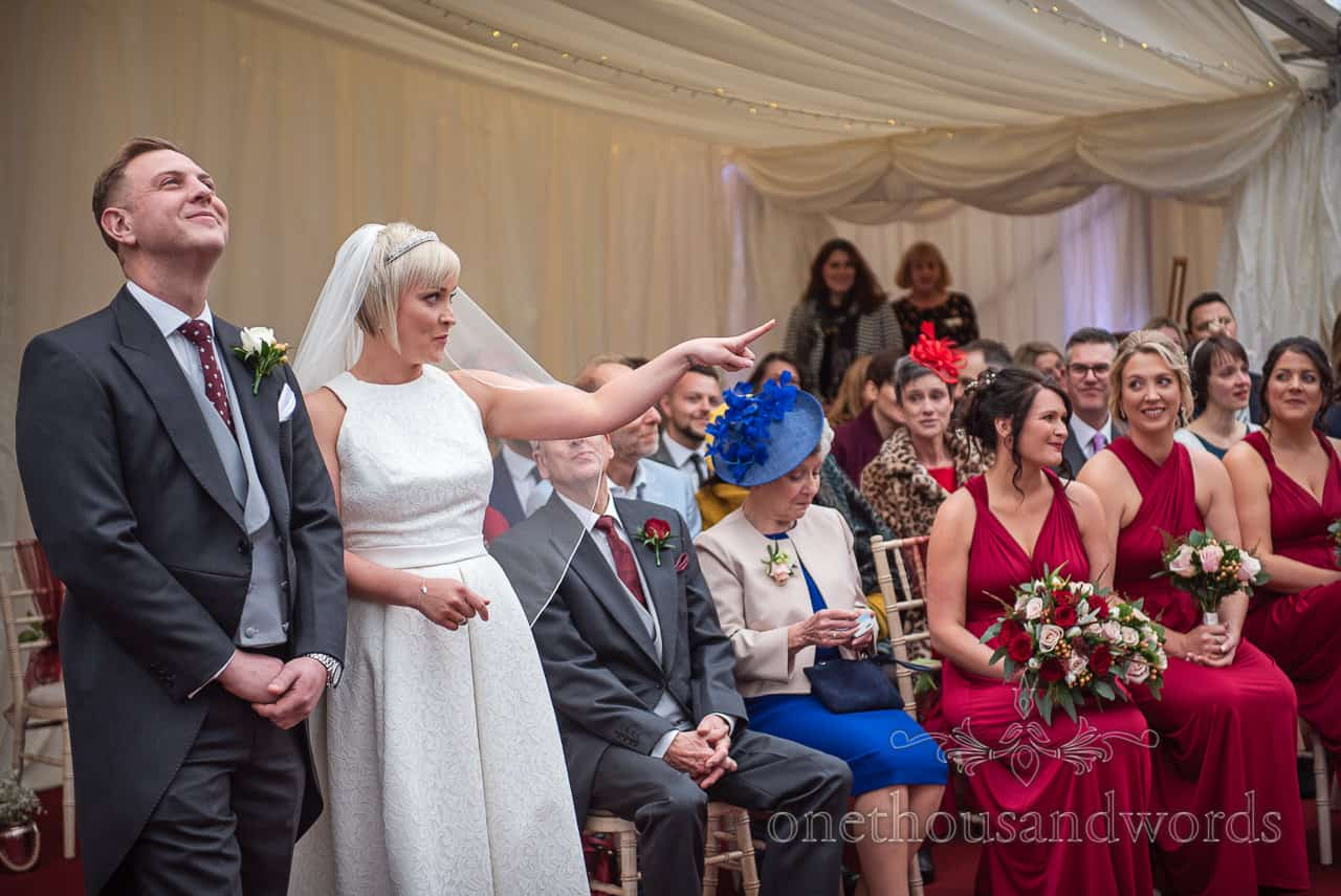 Bride and groom react to reading at Smedmore House marquee wedding ceremony