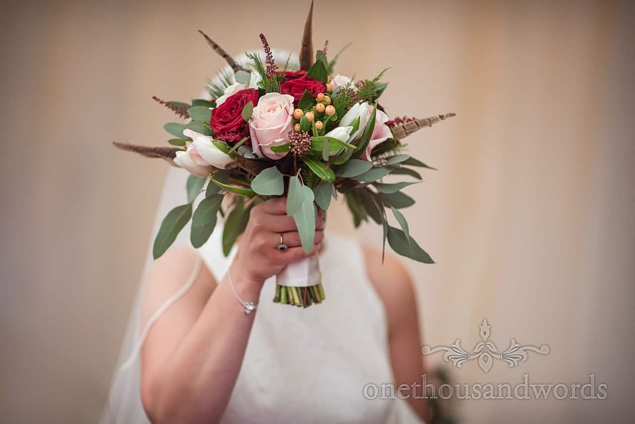Bride hides behind floral bridal bouquet at Smedmore House wedding