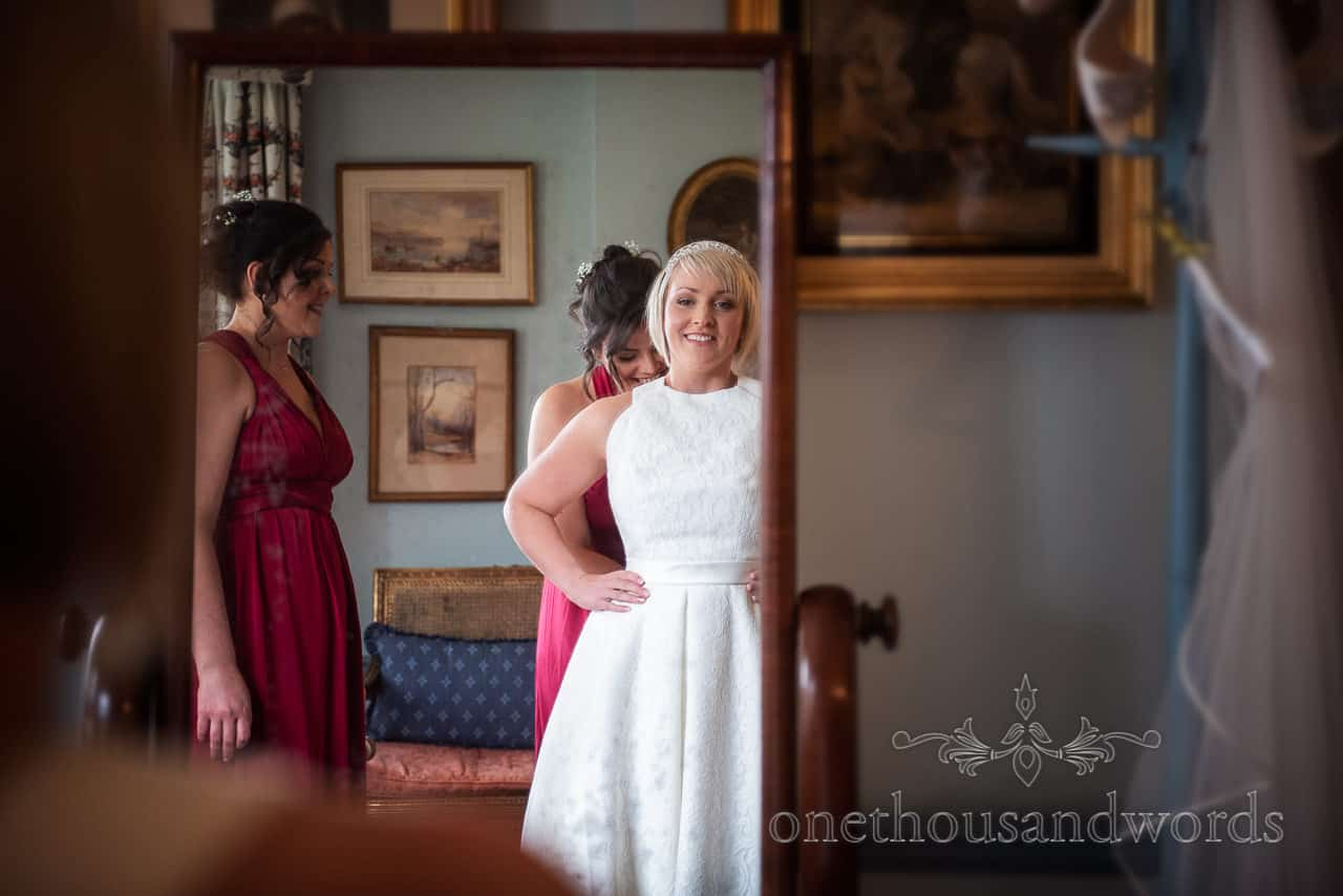 Bride looking mirror while bridesmaids assists on Smedmore House wedding morning