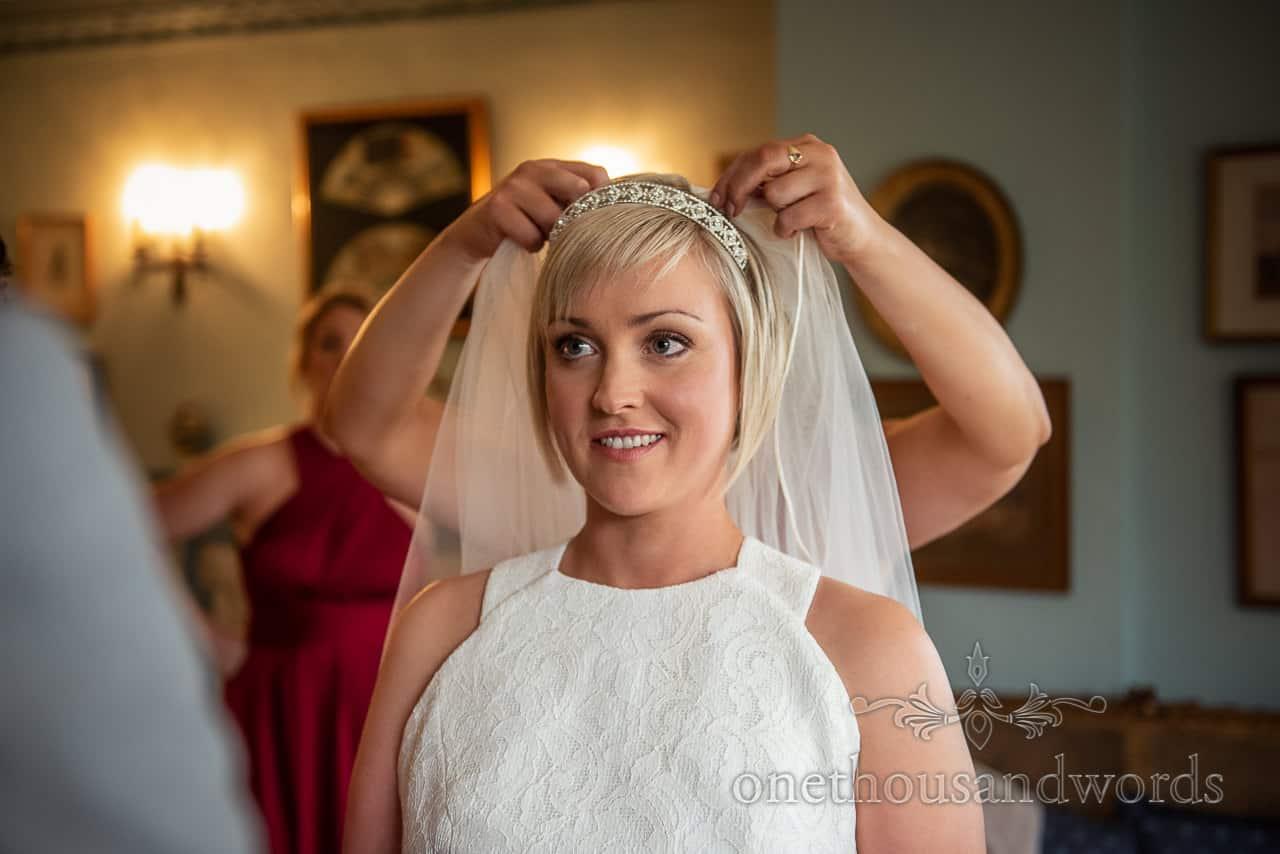 Bridesmaid adjusts brides veil Smedmore House wedding morning