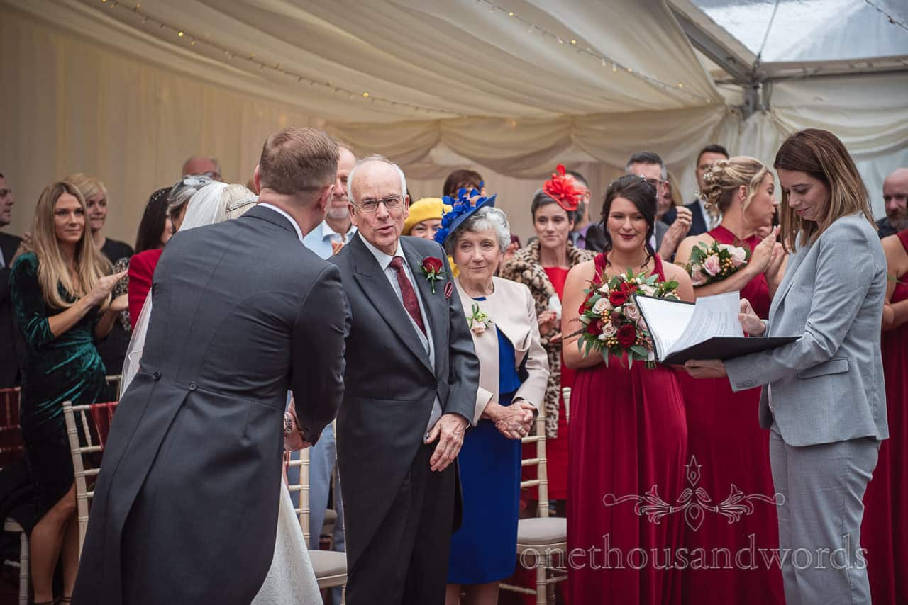 Father of the bride shakes hand of son in-law to be at Smedmore House marquee wedding ceremony