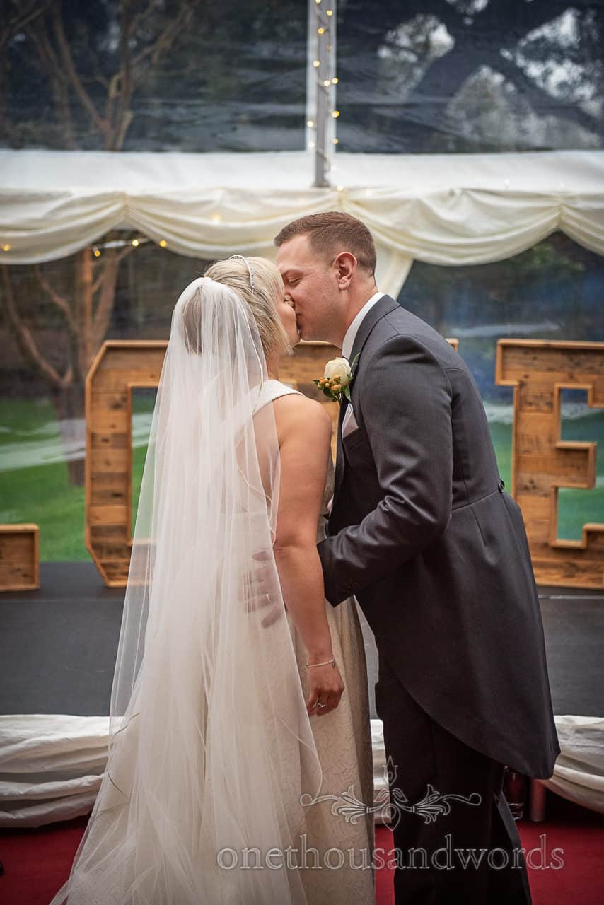 Bride and groom first kiss Smedmore House wedding marquee ceremony