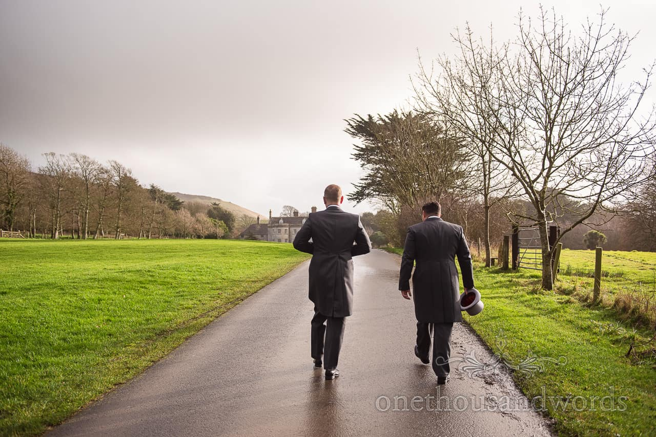 Groom and best man walk up driveway Smedmore House wedding venue