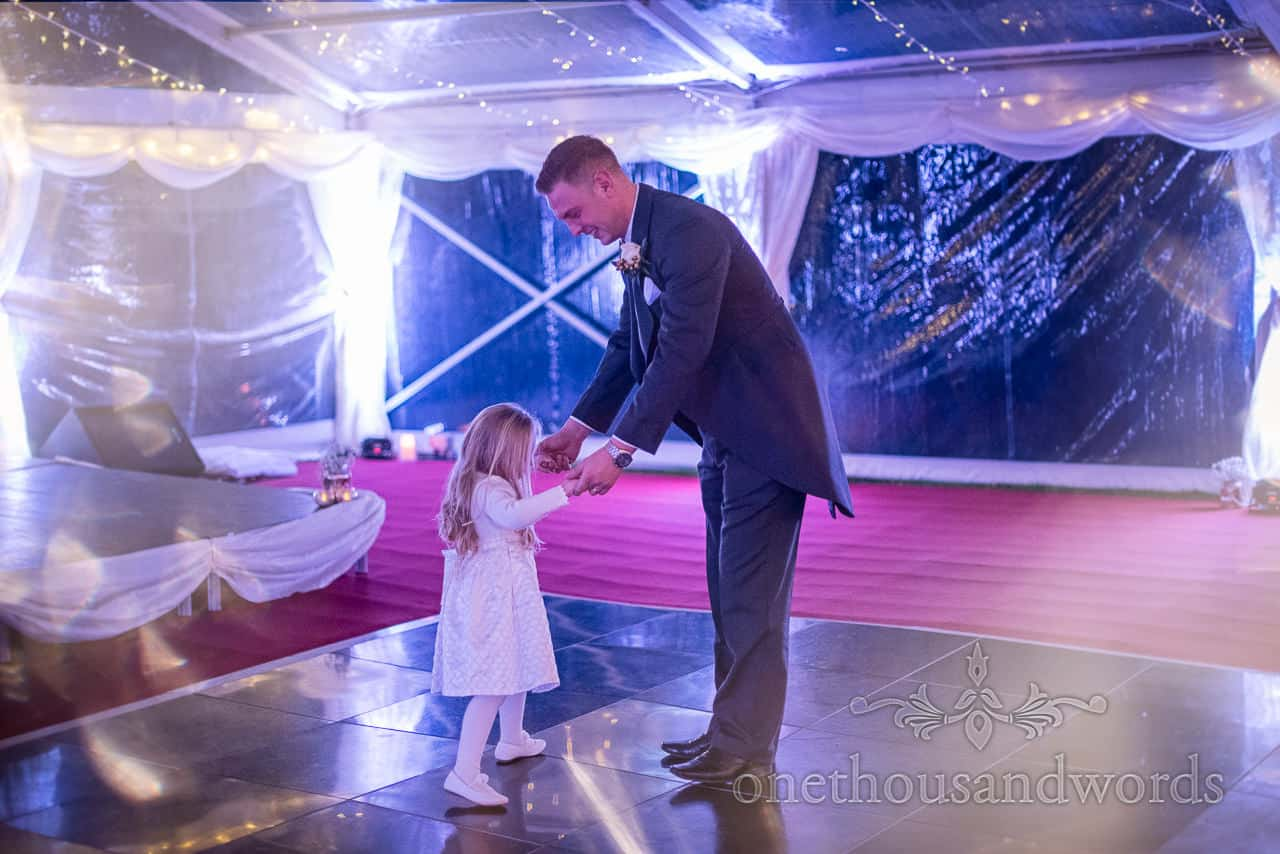 Groom dances with flower girl at Smedmore House marquee wedding reception