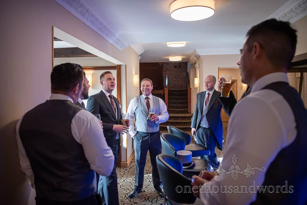 Groom and groomsmen enjoy drink hotel bar before Smedmore House wedding