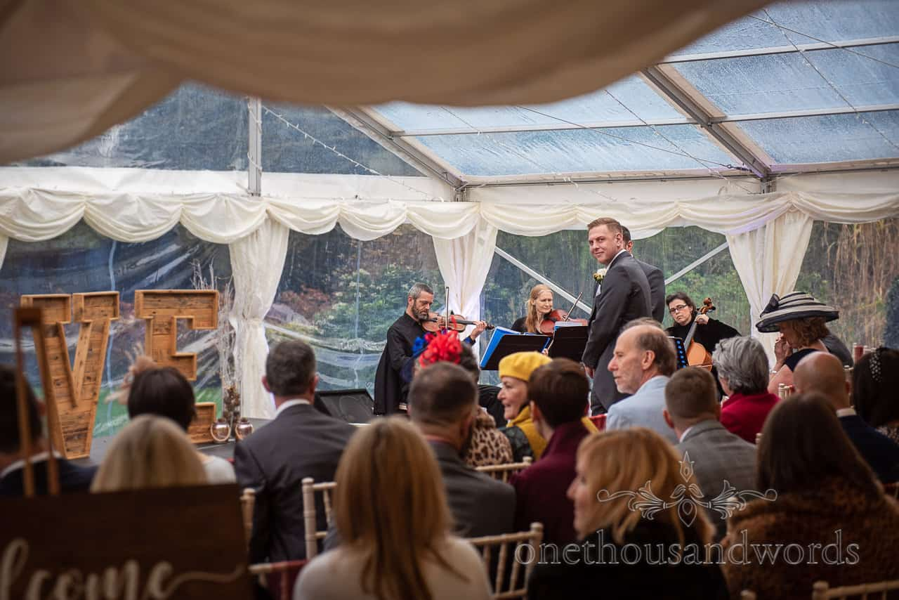 Groom looks towards entrance at Smedmore House marquee wedding