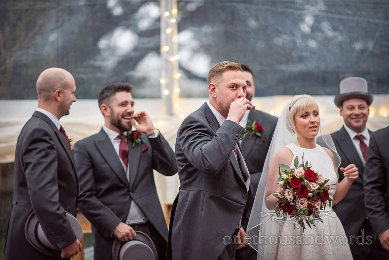 Groom takes drink from hip flask Smedmore House wedding reception
